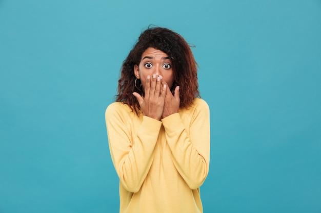 Schockierte afrikanische frau im pullover, der ihren mund bedeckt