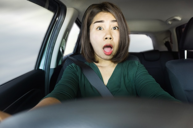 Schockierte asiatische frau, die autounfallursache fährt