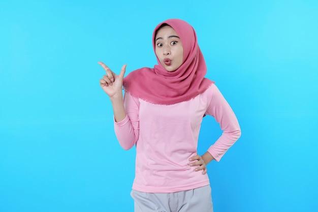Schockierte asiatische frau mit dem finger, die isoliert auf hellblauem hintergrund zeigt, trägt hijab mit rosa t-shirt