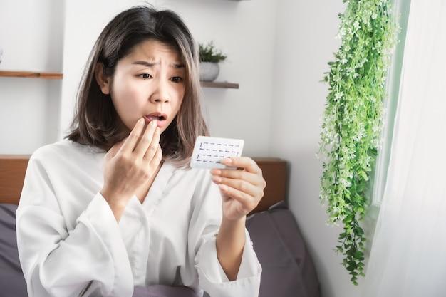 Schockierte asiatische frau vergessen, verhütungspille zu nehmen