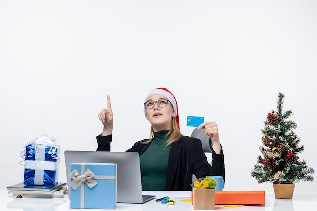 Schockierte attraktive frau mit weihnachtsmannhut und tragenden brillen, die an einem tischweihnachtsgeschenk sitzen und bankkarte halten, die oben im büro zeigt