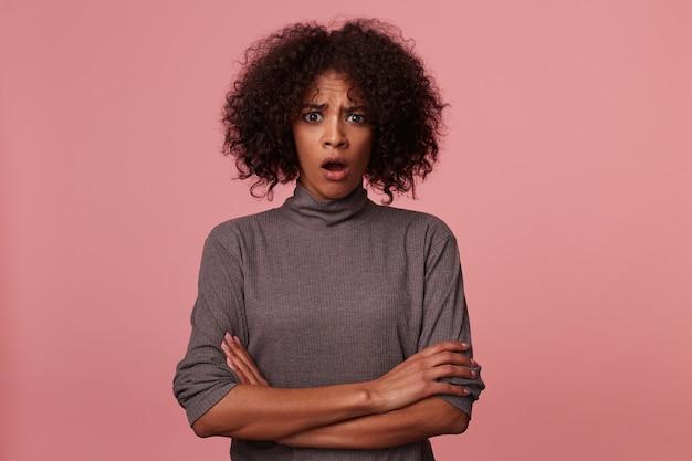 Schockierte attraktive junge dunkelhäutige brünette dame mit kurzen lockigen haaren, die mit ärgerlichem gesicht aussehen, faltige stirn mit geöffnetem mund beim posieren