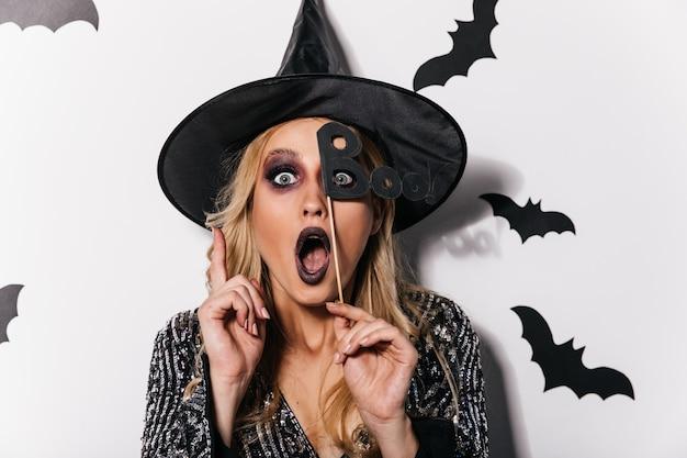 Schockierte blonde frau im zaubererhut, der an halloween-partei aufwirft. weißes mädchen im hexenkostüm, das erstaunen ausdrückt.
