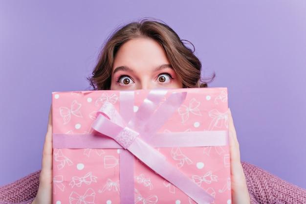 Schockierte braunäugige frau, die großes geburtstagsgeschenk vor gesicht hält. nahaufnahmeporträt des verblüfften brünetten mädchens mit rosa weihnachtsgeschenk auf vordergrund.
