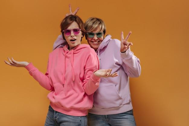 Schockierte brünette dame in der sonnenbrille und im rosa sweatshirt, die in die kamera schauen und mit der fröhlichen frau darstellen, die friedenszeichen auf orange hintergrund zeigt.