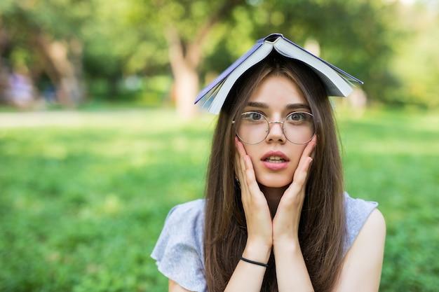 Schockierte brünette frau, die im park mit buch auf kopf sitzt, während sie ihre arme auf wangen hält und in die kamera schaut