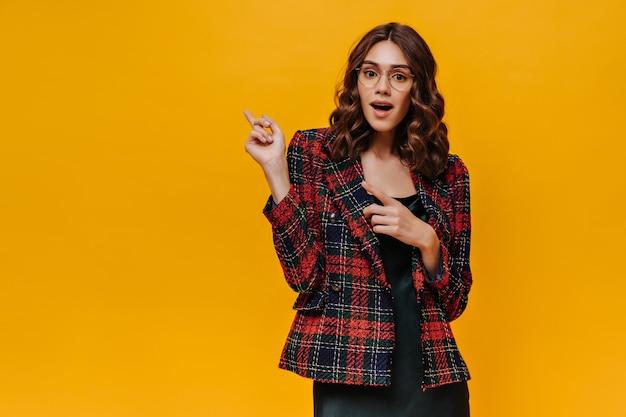Schockierte dame mit brille und gestreiftem outfit, die zum platzieren von text an einer isolierten wand zeigt