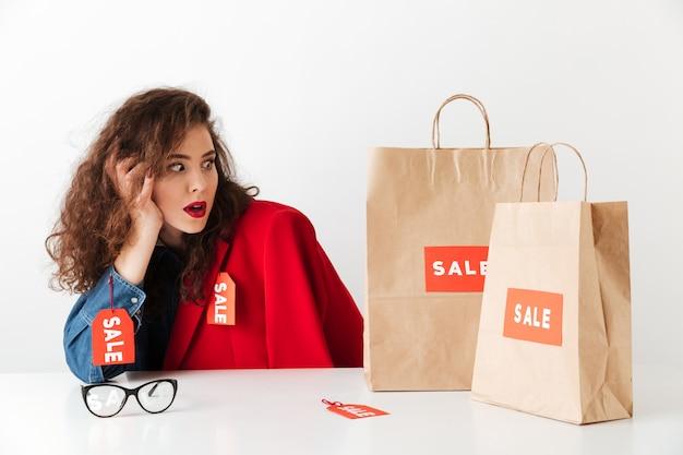 Schockierte einkaufsverkaufsfrau, die mit papiereinkaufstüten sitzt