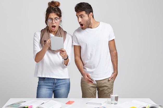 Schockierte emotionale frau und mann überrascht, fehler beim aktualisieren der software und beim installieren der anwendung zu haben