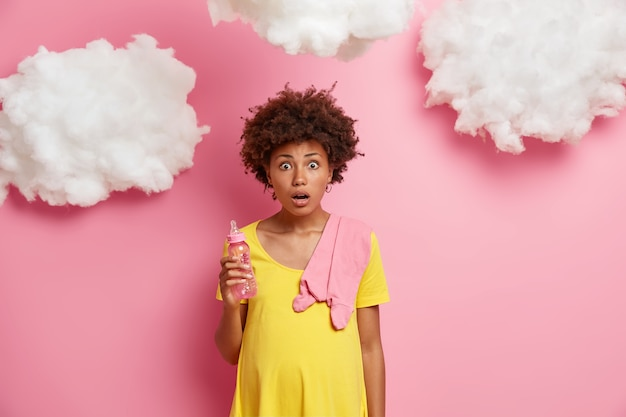 Schockierte emotionale schwangere frau in gelbem kleid, hat runden bauch, posiert mit babyartikeln, realisiert zwei wochen vor der entbindung, fast neun monate mit aufregenden erwartungen hinter sich.