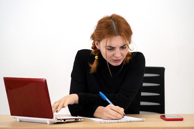 Schockierte ernsthafte junge büroangestellte frau, die hinter schreibtisch mit laptop-computer, handy und notizbuch sitzt.