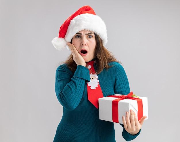 Schockierte erwachsene kaukasische frau mit weihnachtsmütze und weihnachtsmann-krawatte legt die hand auf das gesicht und hält die weihnachtsgeschenkbox isoliert auf weißer wand mit kopierraum