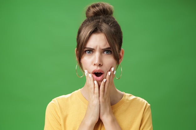 Schockierte frau, die auf pickel reagiert, die im spiegel verstört und unzufrieden aussieht und sich an den händen hält...