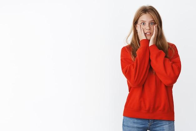Schockierte frau, die mit empathie auf einen freund schaut, der schreckliche nachrichten erzählt, die handflächen an die wangen pressen, die zähne zusammenbeißen und besorgt keuchen, sich nervös und besorgt fühlen und einen süßen roten pullover tragen