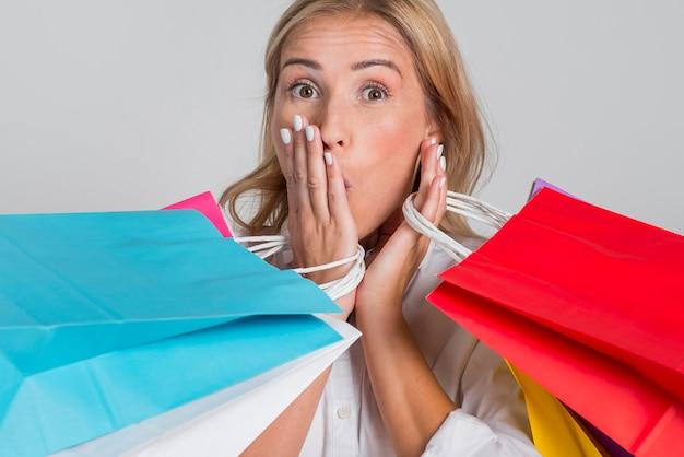Schockierte frau, die mit vielen bunten einkaufstaschen aufwirft