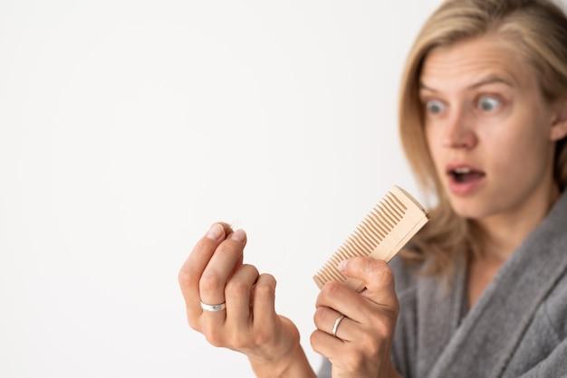 Schockierte frau, die sich die haare bürstet, die an haarausfall leidet