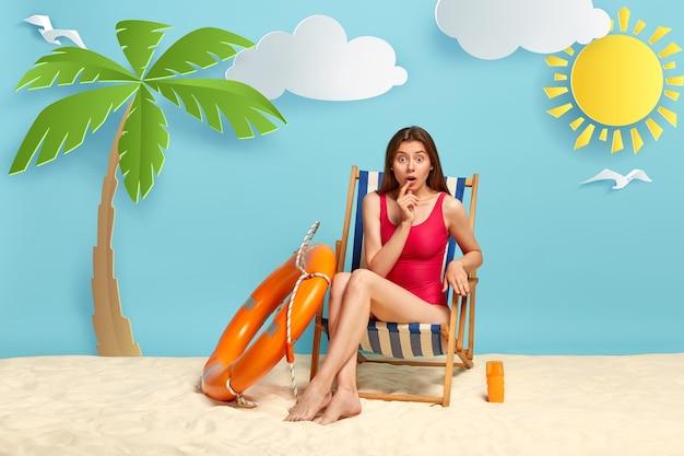 Schockierte frau entspannt sich am strand, ruht auf der liege, genießt den sommer