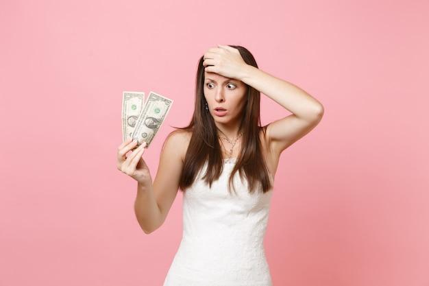Schockierte frau im weißen kleid, die hand auf der stirn hält und ein-dollar-scheine hält