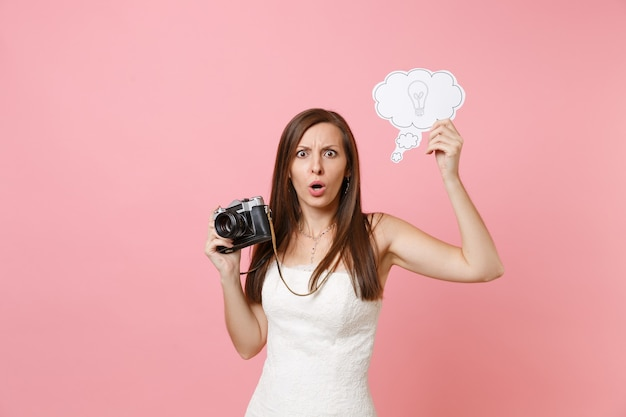 Schockierte frau im weißen kleid hält retro-vintage-fotokamera, sagen sie cloud-sprechblase mit glühbirne, die personal wählt