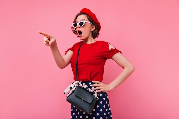 Schockierte frau in weißen gläsern, die in der roten baskenmütze aufwerfen. emotionale französische dame stehend.