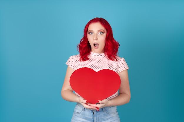 Schockierte frau mit roten haaren und offenem mund hält ein großes rotes papierherz in zwei händen