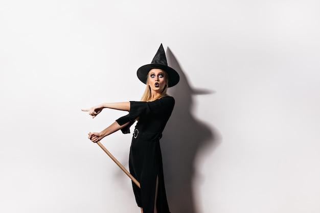 Schockierte frau mit schwarzen lippen, die am karneval aufwerfen. emotionales mädchen im hexenkostüm, das halloween feiert.