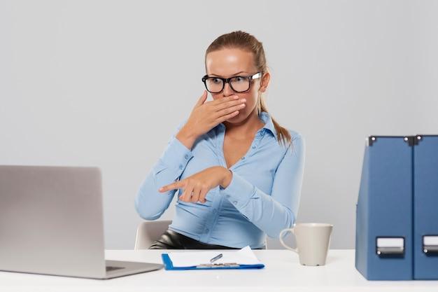 Schockierte frau zeigt auf laptop