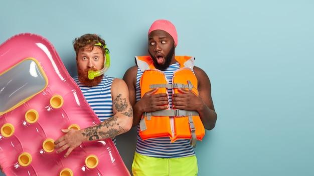 Schockierte freunde posieren mit strandartikeln