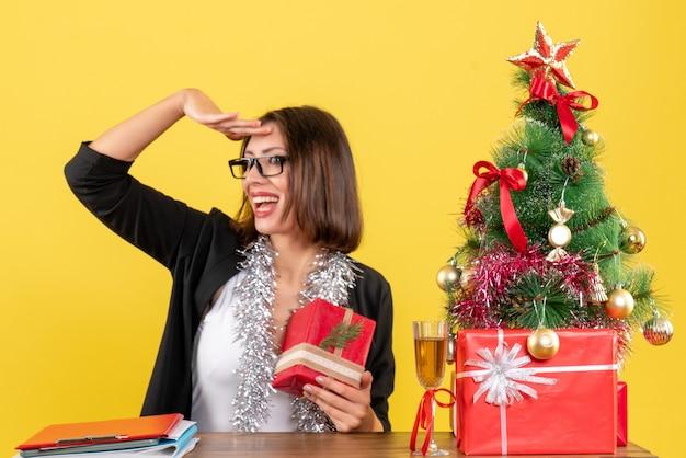 Schockierte geschäftsdame im anzug mit brille, die ihr geschenk hält und an einem tisch mit einem weihnachtsbaum darauf im büro sitzt