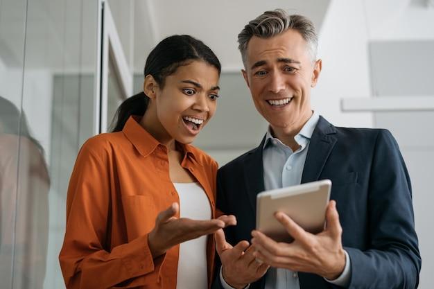Schockierte geschäftsleute, die digitales tablett betrachten, das bildschirm betrachtet und nachrichten liest, die im büro arbeiten