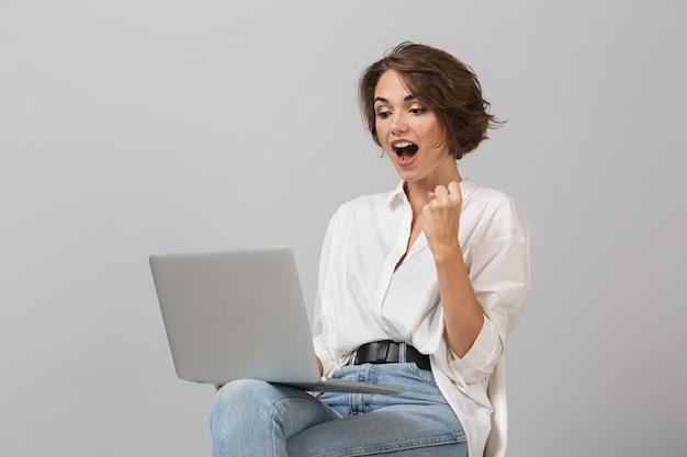 Schockierte glückliche junge frau, die auf hocker lokalisiert über grauer wand hält, die laptop-computer hält