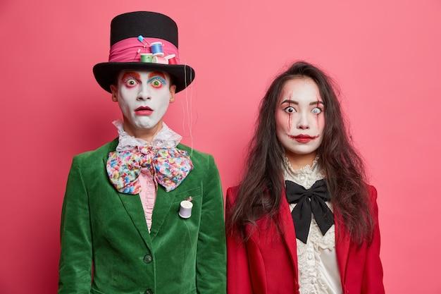 Schockierte gruselige paare feiern halloween haben professionelle make-up und tragen kostüme nebeneinander gegen rosa wand
