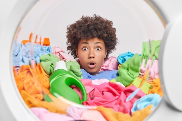 Schockierte hausfrau mit lockigem haar steckt den kopf durch einen haufen wäsche posiert in der waschmaschinentür in der nähe einer waschmittelflasche, die beim waschen beschäftigt ist, kann ihren augen nicht trauen, schmutzige mehrfarbige kleidung zu laden
