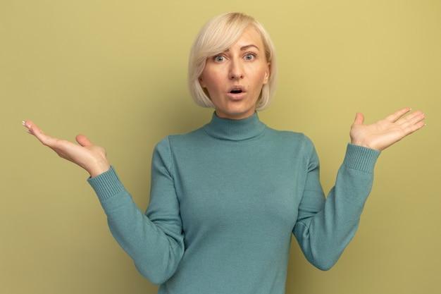 Schockierte hübsche blonde slawische frau hält hände offen auf olivgrün