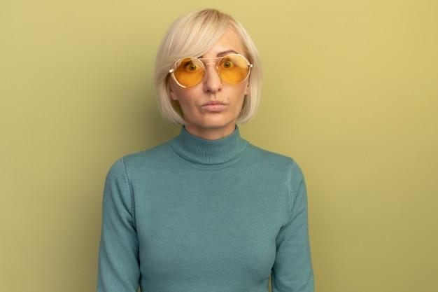Schockierte hübsche blonde slawische frau in der sonnenbrille betrachtet kamera auf olivgrün