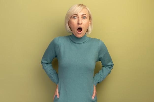 Schockierte hübsche blonde slawische frau legt hände auf taille und schaut nach vorne isoliert auf olivgrüner wand