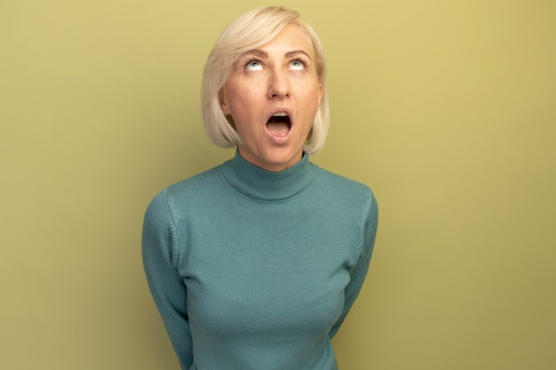 Schockierte hübsche blonde slawische frau schaut isoliert auf olivgrüner wand auf