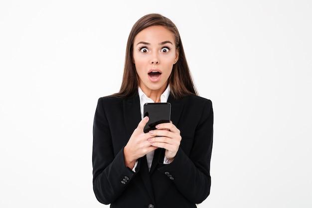 Schockierte hübsche geschäftsfrau, die telefonisch plaudert