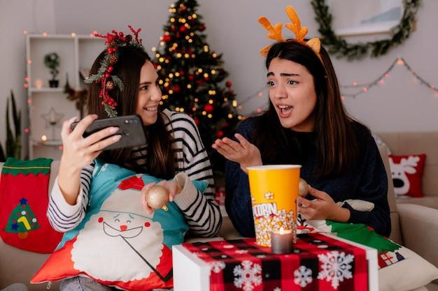 Schockierte hübsche junge mädchen mit stechpalmenkranz und rentierstirnband schauen auf das telefon, das auf sesseln sitzt und die weihnachtszeit zu hause genießt