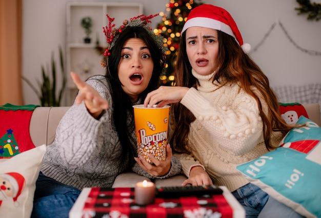 Schockierte hübsche junge mädchen mit weihnachtsmütze und stechpalmenkranz essen popcorn auf sesseln sitzen und genießen die weihnachtszeit zu hause