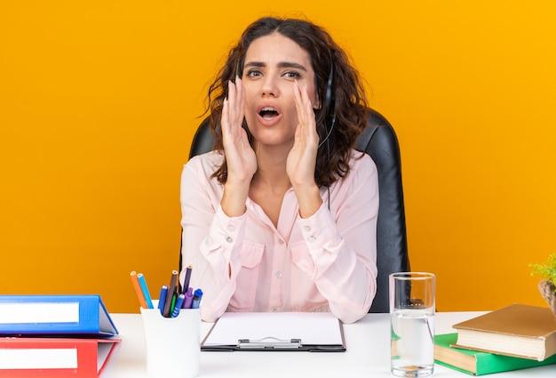 Schockierte hübsche kaukasische callcenter-betreiberin auf kopfhörern, die am schreibtisch mit bürowerkzeugen sitzen, die die hände nah an ihrem mund halten