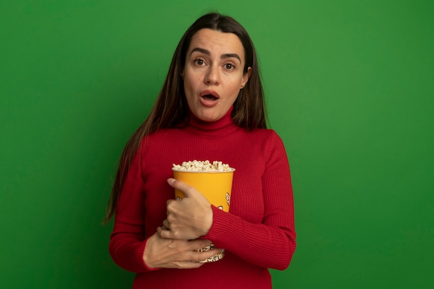 Schockierte hübsche kaukasische frau hält eimer popcorn auf grün