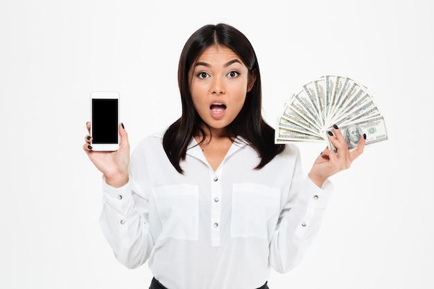 Schockierte junge asiatische frau, die geld hält, das anzeige des telefons zeigt.