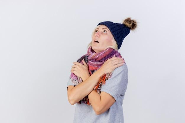 Schockierte junge blonde kranke frau, die wintermütze und schal trägt, hält arme, die lokal auf weißer wand suchen