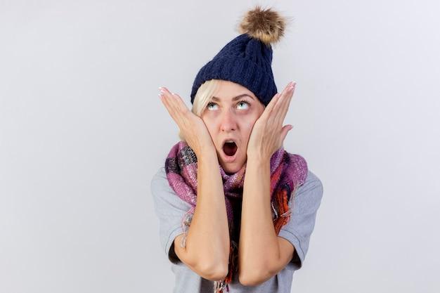 Schockierte junge blonde kranke frau, die wintermütze und schal trägt, legt hände auf gesicht, das lokalisiert auf weißer wand schaut