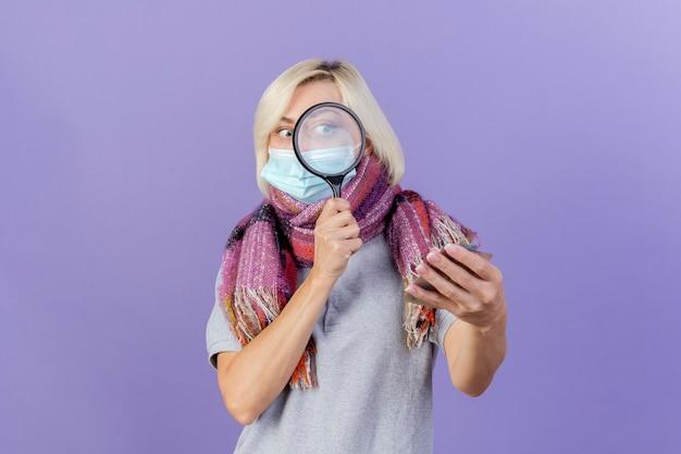 Schockierte junge blonde kranke slawische frau, die medizinische maske und schal trägt