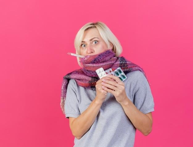 Schockierte junge blonde kranke slawische frau, die schal trägt, hält packungen mit medizinischen pillen, die messen