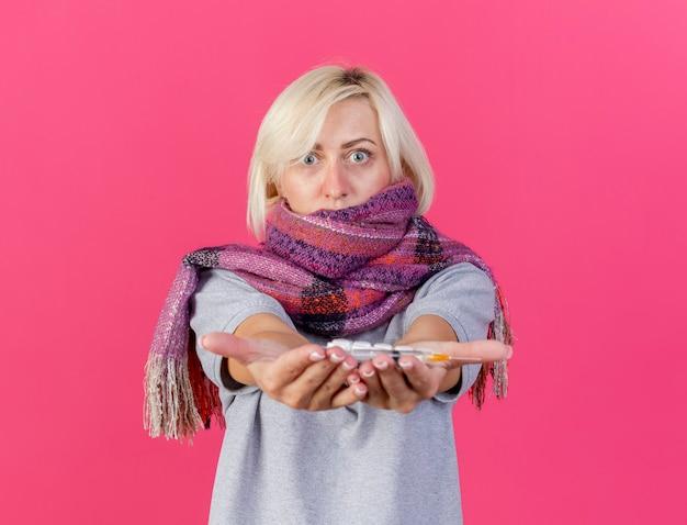 Schockierte junge blonde kranke slawische frau, die schal trägt, hält packungen mit medizinischen pillen