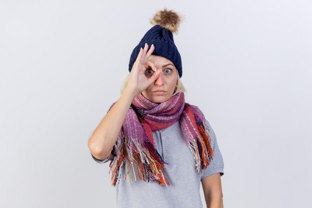 Schockierte junge blonde kranke slawische frau, die wintermütze und schal trägt, betrachtet kamera durch finger lokalisiert auf weißer wand mit kopienraum