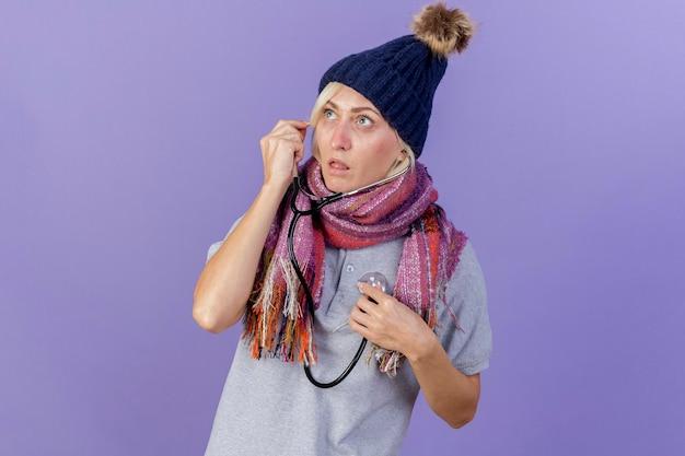 Schockierte junge blonde kranke slawische frau, die wintermütze und schal trägt